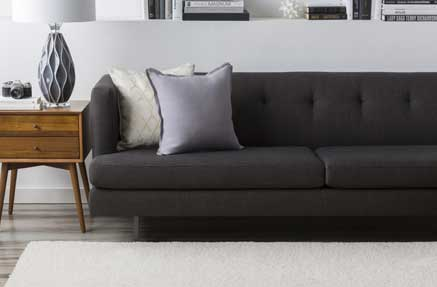 A contemporary living room with a grey sofa and cushions