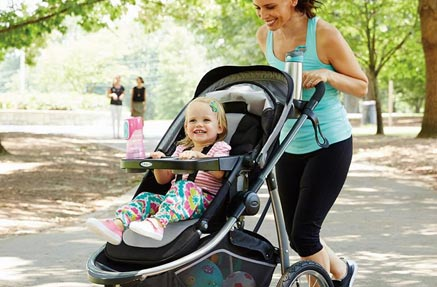 A mother pushing her baby in stroller.