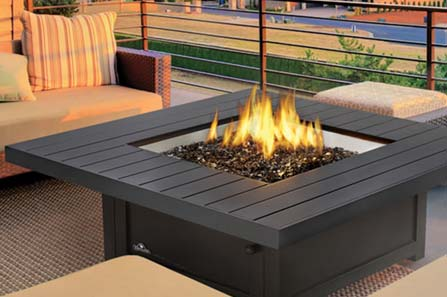 An outdoor firepit surrounded by patio furniture