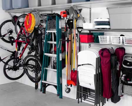 an organized wall in a garage using monkey bar storage shelving and racks