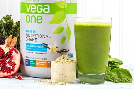 A jar of Vega One Nutritional Shake next to a glass of green smoothy and a scoop of the powder
