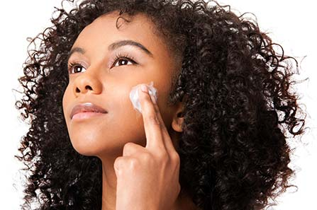 A woman applying face cream to her cheek