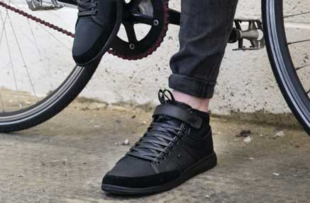 Close up of a man wearing black casual sneakers and leaning against a bicycle