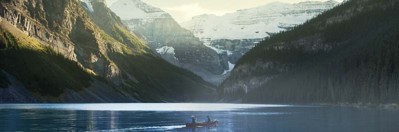Two people canoeing on a lake with a scenic mountain background